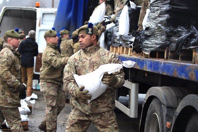 Soldados descargan sacos de arena para contener las inundaciones en Reino Unido