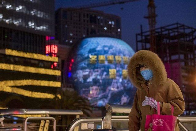 Una mujer pasea por las calles de Shangahi ataviada con una de las mascarillas que las autoridades chinas recomiendan llevar para evitar el contagio del nuevo coronavirus.