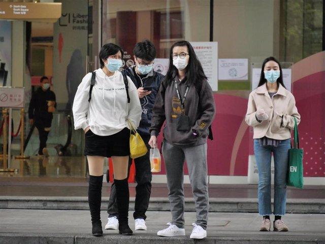 Pasajeros esperan con mascarillas en una estación de tren de China.