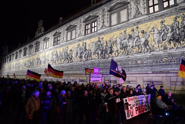 17 February 2020, Saxony, Dresden: Supporters of the anti-Islam and xenophobicmovement Pegida, pass by the Procession of Princes mural during the movement's 200th rally. Photo: Robert Michael/dpa-Zentralbild/dpa
