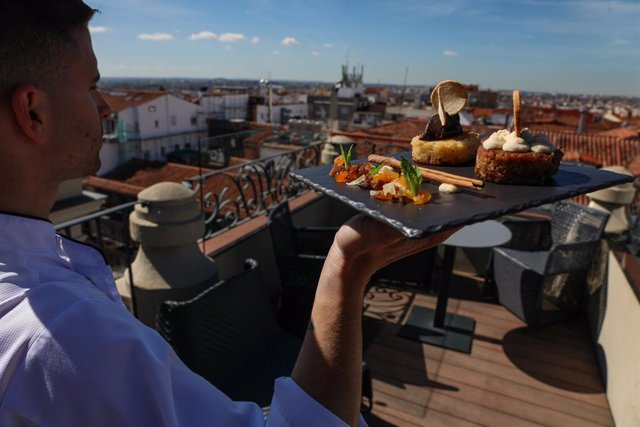 Un camarero lleva una bandeja con dos toriijas del chef Juan Manuel Muñoz, en la terraza del Hotel Catalonia (Calle Atocha 8).