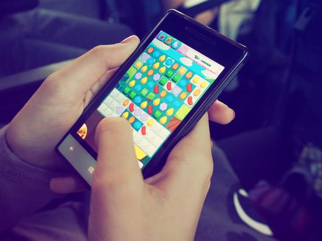 Recurso de persona jugando a un juego en su dispositivo móvil