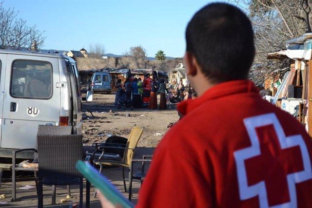 Voluntario de Cruz Roja visita un asentamiento de inmigrantes