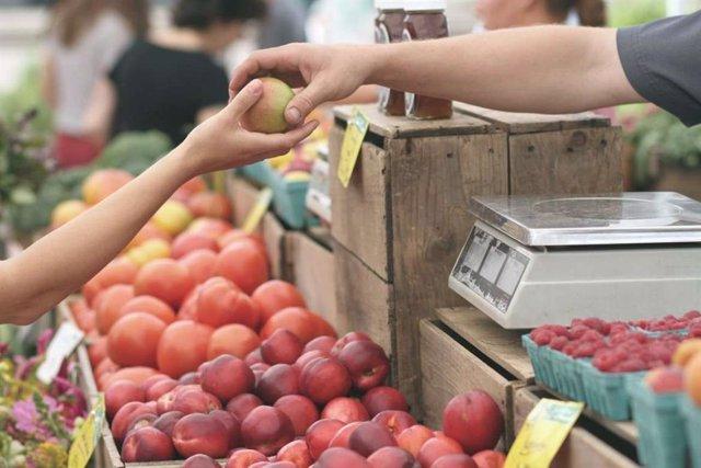 Un tendero entrega una pieza de fruta a un cliente.