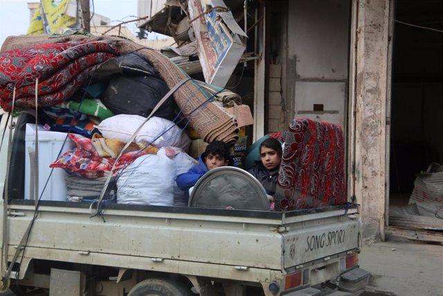 Unos niños sirios en un camión con las pertenencias de su familia huyen de la ofensiva en Idlib