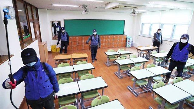 Operarios desinfectan un aula en la ciudad surcoreana de Suwon.