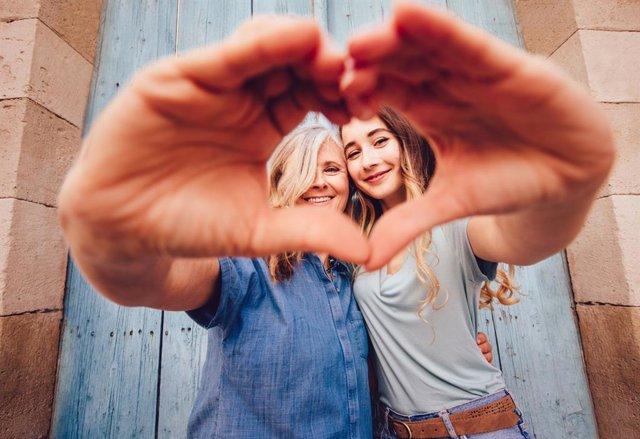 Madre e hija sonríen haciendo el signo del corazón.