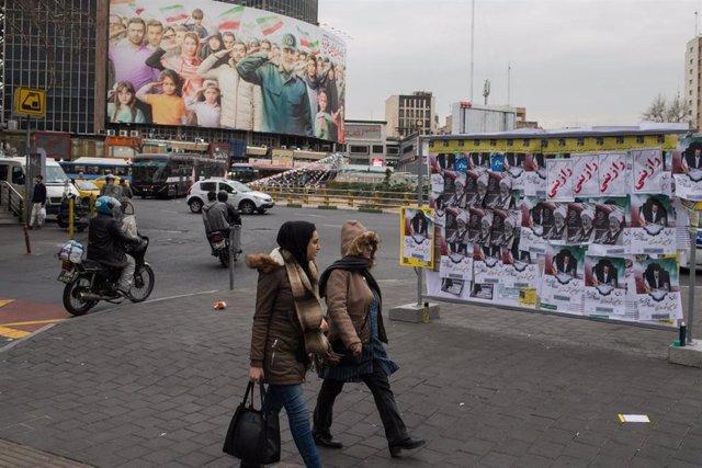 Dos mujeres pasan por delante de carteles electorales en Teherán