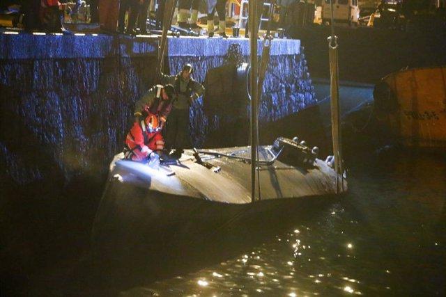 Agentes de la Policía y de la Guardia Civil subidos en el narcosubmarino hundido el pasado fin de semana a la entrada de la ría de Aldán, en Cangas (Pontevedra) en el momento en el que estaba siendo reflotado por dos grandes grúas. Se trata del primer nar
