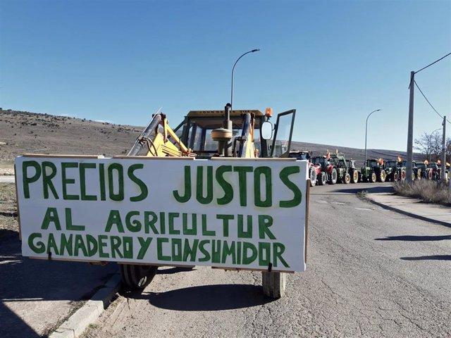 """Uno de los tractores de la tractorada de agricultores y ganaderos de Molina de Aragón (Guadalajara) con un cartel en el que se lee """"Precios justos al agricultor, ganadero y consumidor""""."""