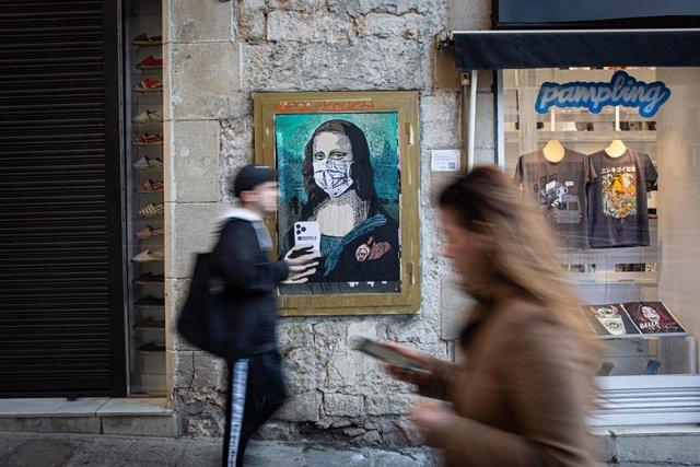 Dos personas pasan con sus móviles junto a una pintura de una Gioconda con un móvil y una mascarilla, obra del grafitero TV Boy llamada 'Mobile World Virus', en referencia a la cancelación del Mobile World Congress a causa del coronavirus, en Barcelona/Ca