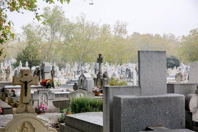 Lápidas con la figura de Cristo en la cruz y  flores en el Cementerio de la Almudena de Madrid.