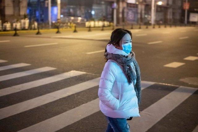 Imagen de una mujer en Shanghái con una mascarilla en medio del brote del nuevo coronavirus.