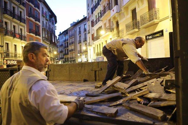 Dos carpinteros preparan las vallas para el sexto encierro de las fiestas de San Fermín con toros de la Ganadería Núñez del Cuvillo en Pamplona.