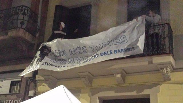 Els activistes col·loquen una pancarta la nit d'aquest dissabte en una balconada de l'edifici després d'ocupar-lo.
