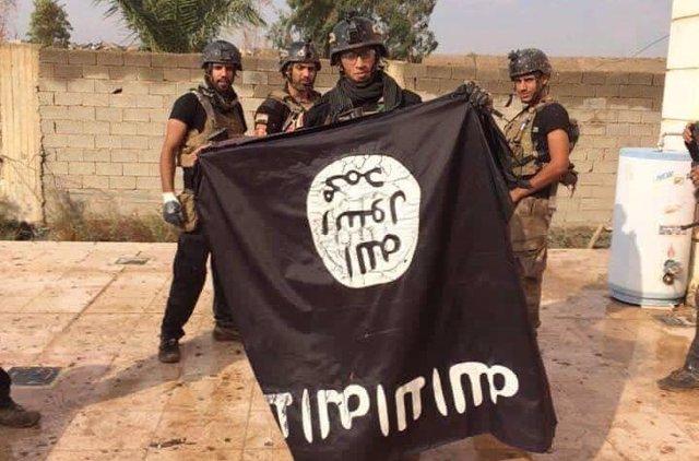 Militares iraquíes sosteniendo una bandera del Estado Islámico