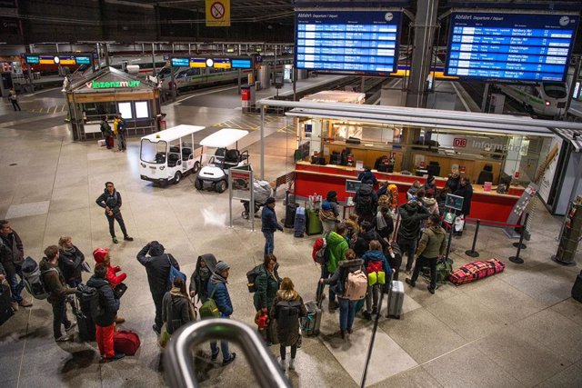 24 February 2020, Bavaria, Munich: Travellers line up at the Deutsche Bahn information desk after a train was stopped at the Brenner Pass for Coronavirus suspicion. Photo: Lino Mirgeler/dpa