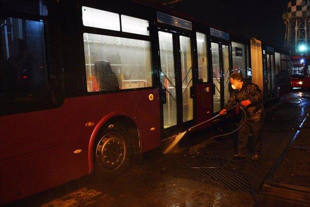 Un trabajador de una compañía de autobuses fumiga un autobús en Teherán