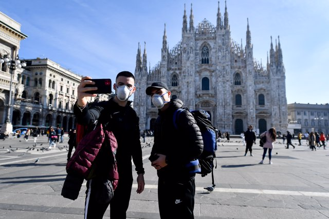 24 February 2020, Italy, Milan: Two tourists take a selfie while wearing surgical masks in front of the Duomo di Milano amid the outbreak of the coronavirus. Photo: Claudio Furlan/LaPresse via ZUMA Press/dpa