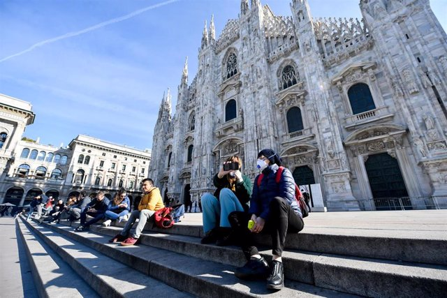 24 February 2020, Italy, Milan: Tourists take sit while wearing surgical masks on the steps of the Duomo di Milano amid the outbreak of the coronavirus. Photo: Claudio Furlan/LaPresse via ZUMA Press/dpa
