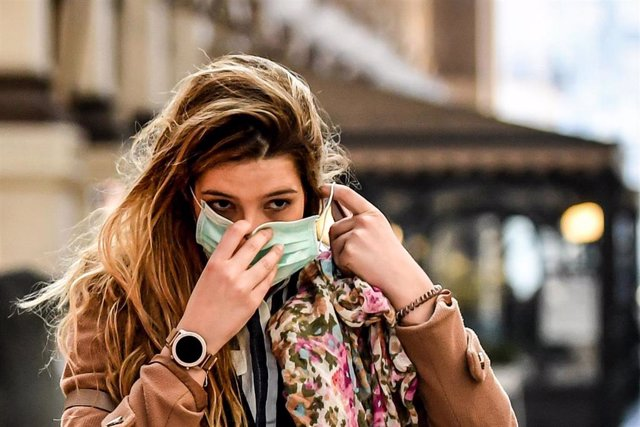 24 February 2020, Italy, Milan: A pedestrian puts on a surgical mask on her face amid the outbreak of the coronavirus. Photo: Claudio Furlan/LaPresse via ZUMA Press/dpa