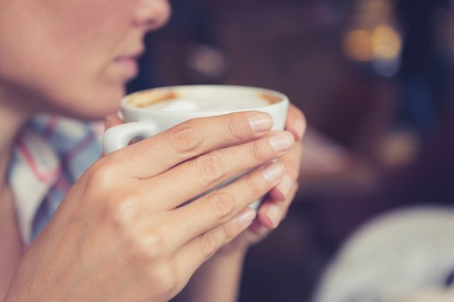 Single. Close up of woman hands holding a cup of coffee, sitting in cafe