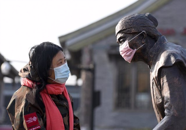 24 February 2020, China, Huai'an: A woman with face mask looks at a sculpture with face mask at cultural corridor of Li Canal. Photo: He Jinghua/SIPA Asia via ZUMA Wire/dpa