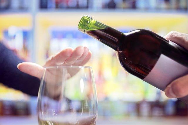 Mujer rechaza beber una copa de vino.