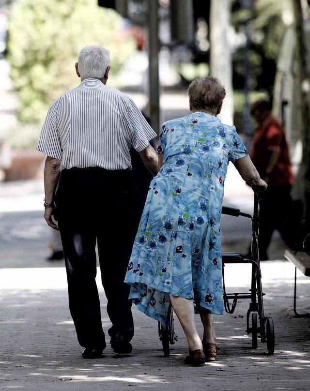 Una pareja de pensionistas pasea con un andador por un parque de Madrid.