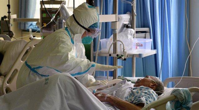 Un médico militar cuida a un enfermo de coronavirus en un hospital en China, a 1 de febrero de 2020.