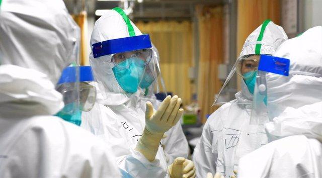 Una enfermera de la unidad de cuidados intensivos explica a sus compañeros de equipo las medidas de seguridad a seguir contra el coronavirus, en China