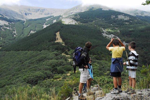 Un guía junto a unos niños en una actividad de senderismo en los Pirineos aragoneses.