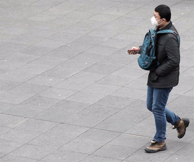 Un hombre asiático pasea con una mascarilla protectora, mientaras las farmacias registran una alta demanda de estas, por parte de ciudadanos chinos tras el coronavirus, en Madrid (España), a 30 de enero/Archivo