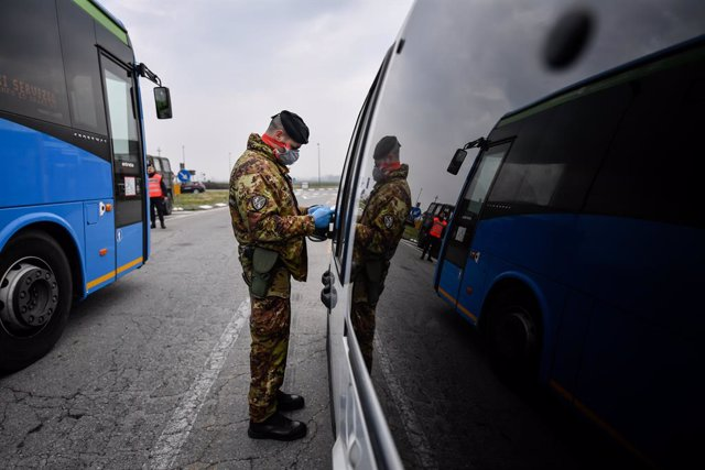 25 February 2020, Italy, Turano Lodigiano: An Italian army soldier with a surgical mask inspects the licence of a driver at a check point amid the outbreak of the coronavirus. Photo: Claudio Furlan/LaPresse via ZUMA Press/dpa