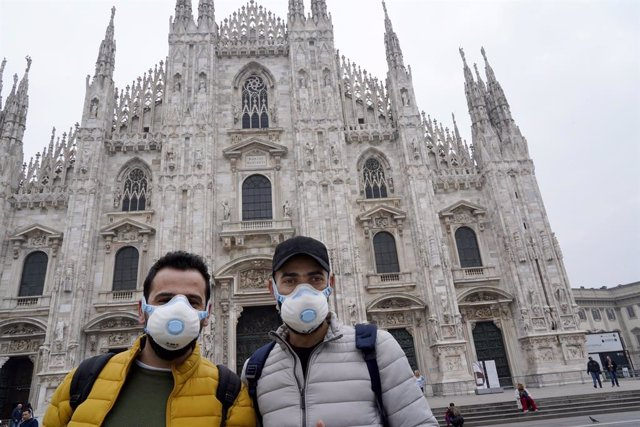 February 25, 2020 - Milan, Italy: Tourists wearing a protective face mask pose for a picture in front of Milan landmark, the Duomo Cathedral. (Lucia Sabatelli/Contacto)