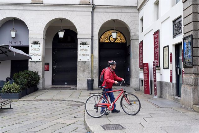 February 25, 2020 - Milan, Italy: A cyclist stops by the Teatro Alla Scala to read a sign informing of the suspension of its programs. Following the order of the Ministry of Health, in agreement with the President of the Lombardy Region, events and initia