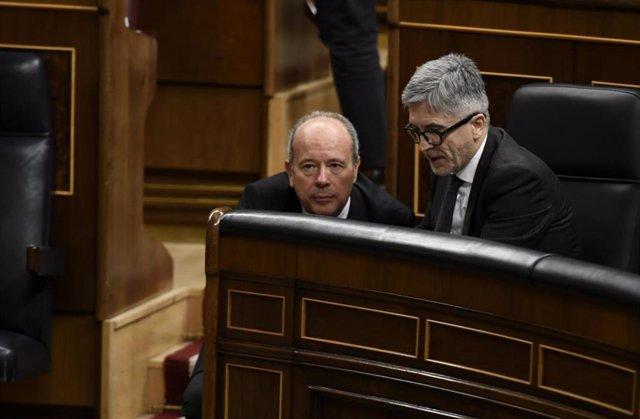 El ministro de Interior, Fernando Grande-Marlaska (dch) mantiene una conversación con el ministro de Justicia, Juan Carlos Campo, (izq) durante una sesión plenaria en el Congreso de los Diputados