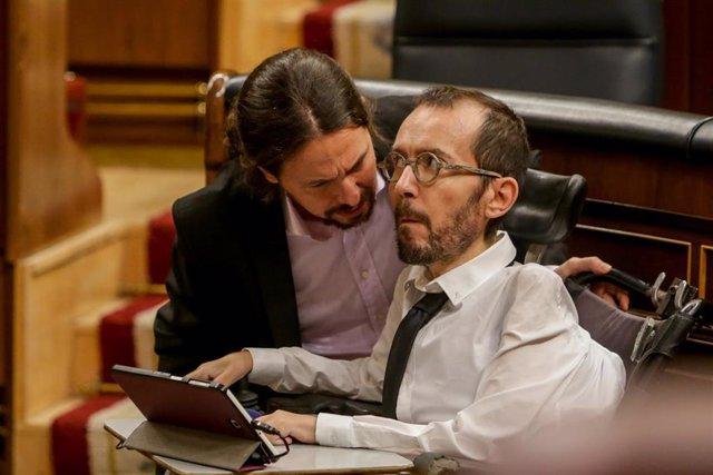 El vicepresidente segundo y ministro de Derechos Sociales y Agenda 2030, Pablo Iglesias (i), habla con el portavoz de Unidas Podemos en el Congreso de los Diputados, Pablo Echenique (d)