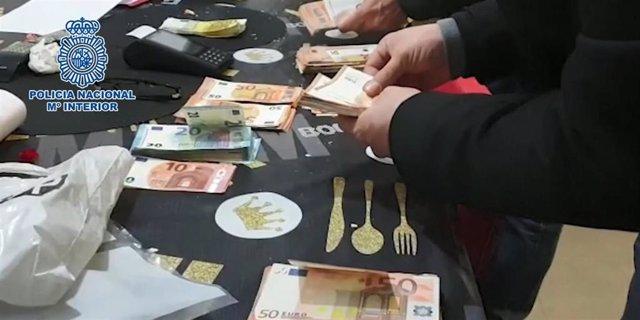 Imagen del dinero y objetos en uno de los registros a una banda desarticulada dedicada a estafas mediante teléfonos móviles.