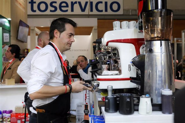 Un camarero prepara café en un bar