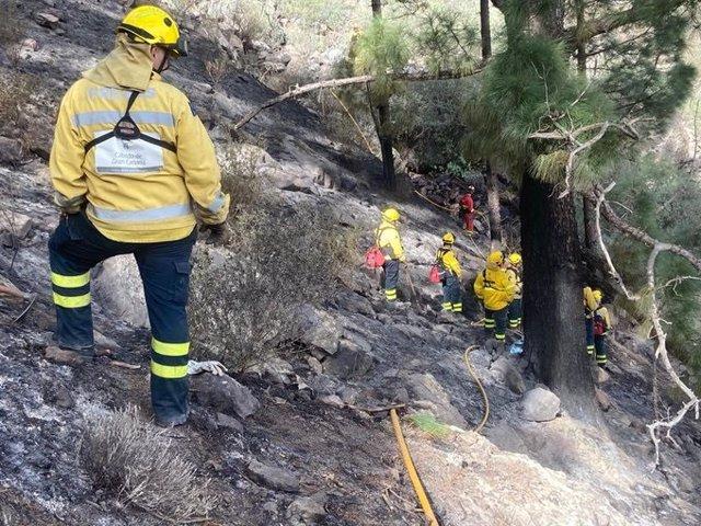 Operarios en las labores de extinción del incendio de Tasarte