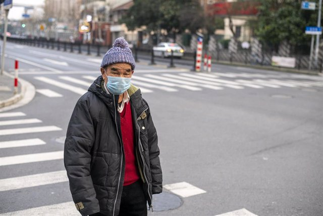 February 25, 2020 - Shanghai China: An elderly man wears a surgical mask as protection against the coronavirus as he crosses a street in Hungpu District According to official figures more than 80,000 people have been infected with the virus and at least 2