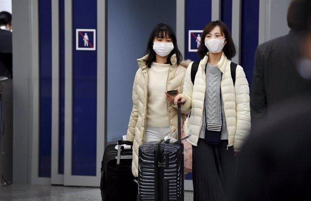 Pasajeros asiáticos con mascarillas a su llegada a un aeropuerto en Finlandia