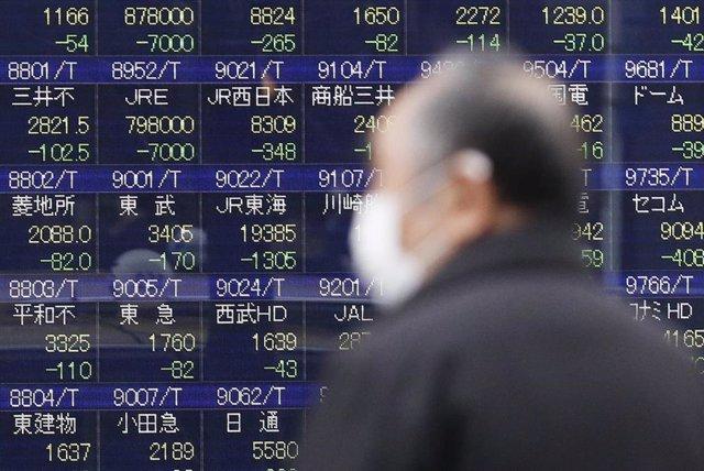 Un hombre con mascarilla en la Bolsa de Tokio