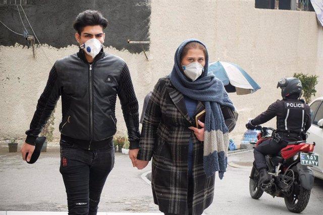 Una pareja con mascarillas en Teherán