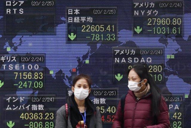 Dos mujeres con mascarilla ante una pantalla mostrando los valores del Nikkei, la bolsa japonesa, en Tokio