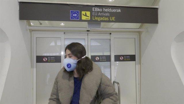 Pasajera, con mascarilla, llega al aeropuero de Bilbao procedente de Milán.