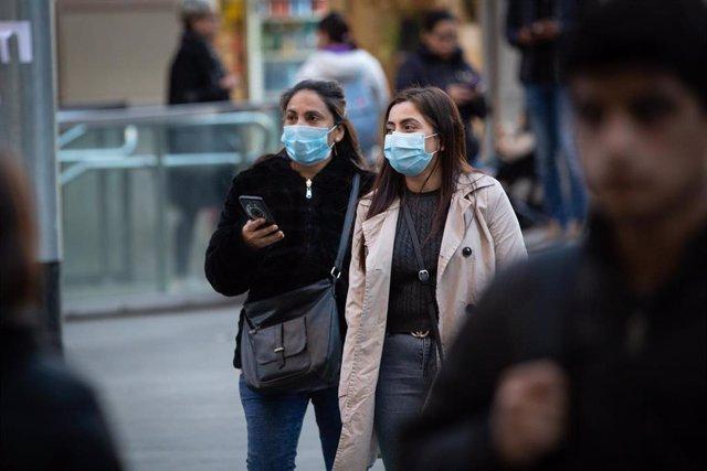 Dos mujeres con mascarillas caminan por Barcelona el mismo día en que se confirman nuevos casos de pacientes contagiados de coronavirus en España, en Barcelona