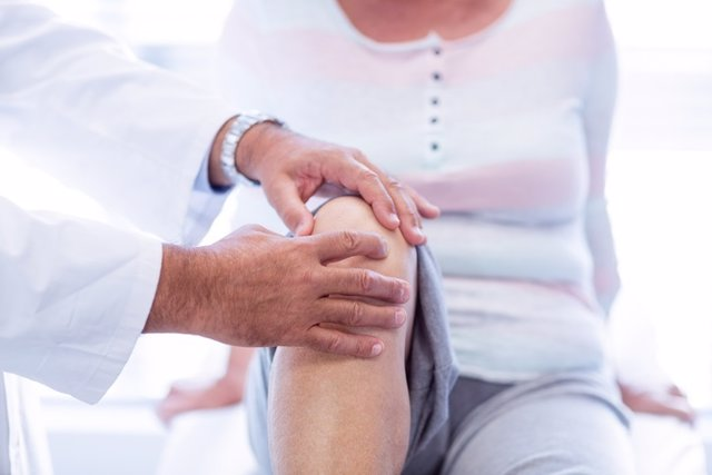 Physiotherapist giving knee therapy to senior woman