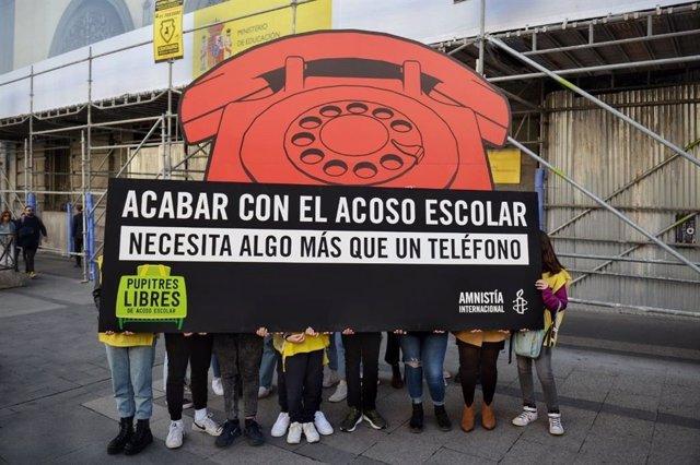 Amnistía Internacional despliega un teléfono gigante ante Educación para denunciar el actual sistema de acoso escolar